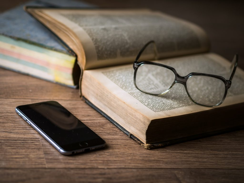 Image books with glasses and phone on a table.